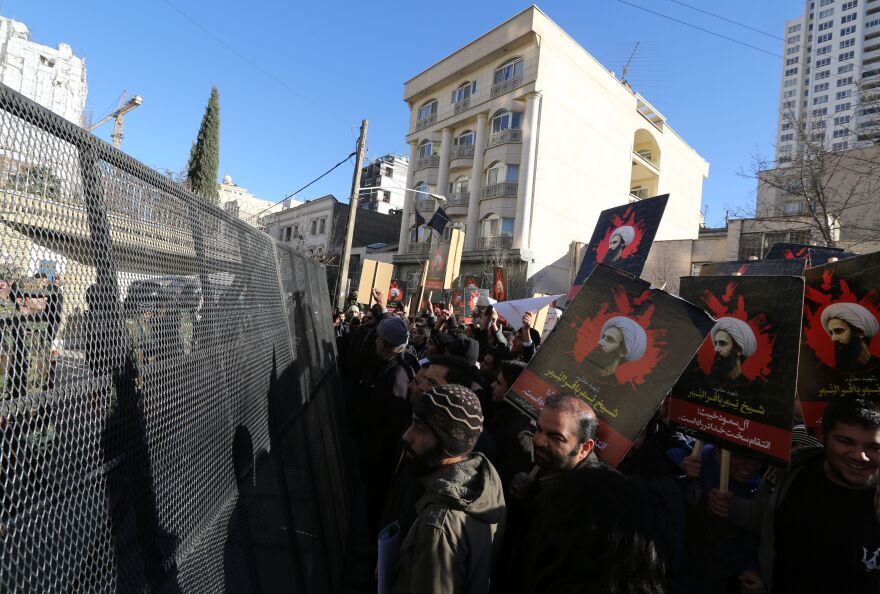 Iranian riot police block a street leading to the Saudi Embassy as protesters hold portraits of prominent Shiite Muslim cleric Nimr al-Nimr during a demonstration against his execution by Saudi authorities on Sunday in Tehran.