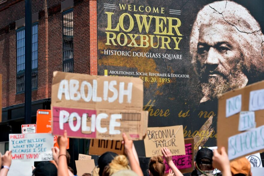Protesters march by a photo of Frederick Douglas, a historic abolitionist, during a Juneteenth protest and march in honor of Rayshard Brooks and other victims of police violence in Boston, Massachusetts. Abolitionists advocate for a world without prisons or police.