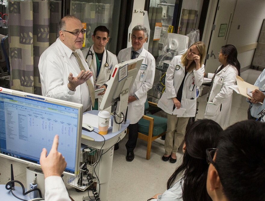 Dr. Paul Marik (left) discusses patient care with medical students and resident physicians during morning rounds at Sentara Norfolk General Hospital in 2014 in Norfolk, Va.