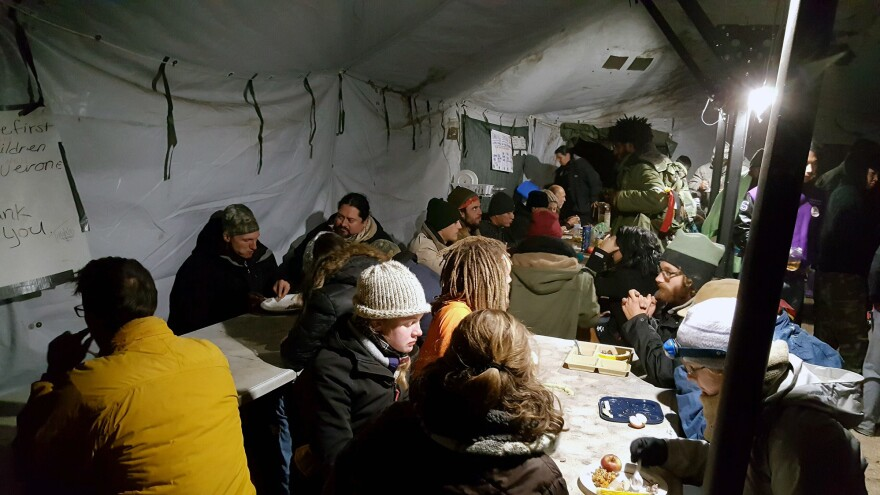 People at the Oceti Sakowin Camp enjoy a meal inside a tent that serves as a dining hall. Oceti Sakowin is the largest of several camps housing demonstrators against the Dakota Access Pipeline.