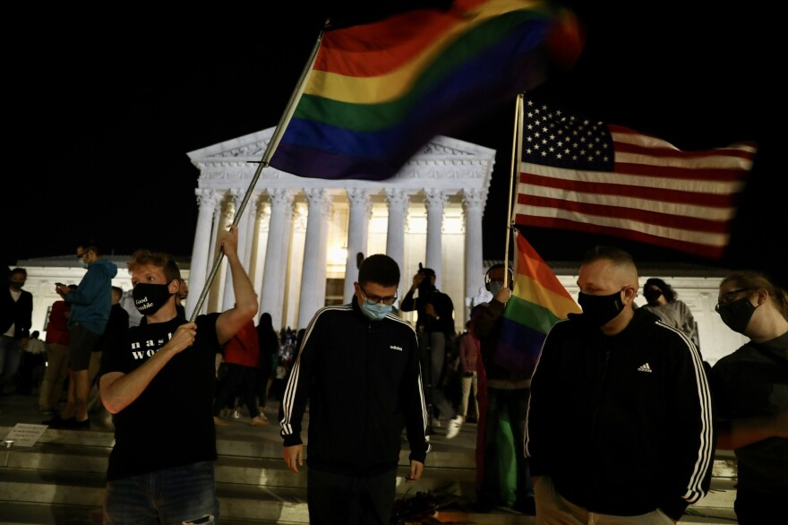 A rainbow flag is waved as people gather at a makeshift memorial for late Justice Ruth Bader Ginsburg.
