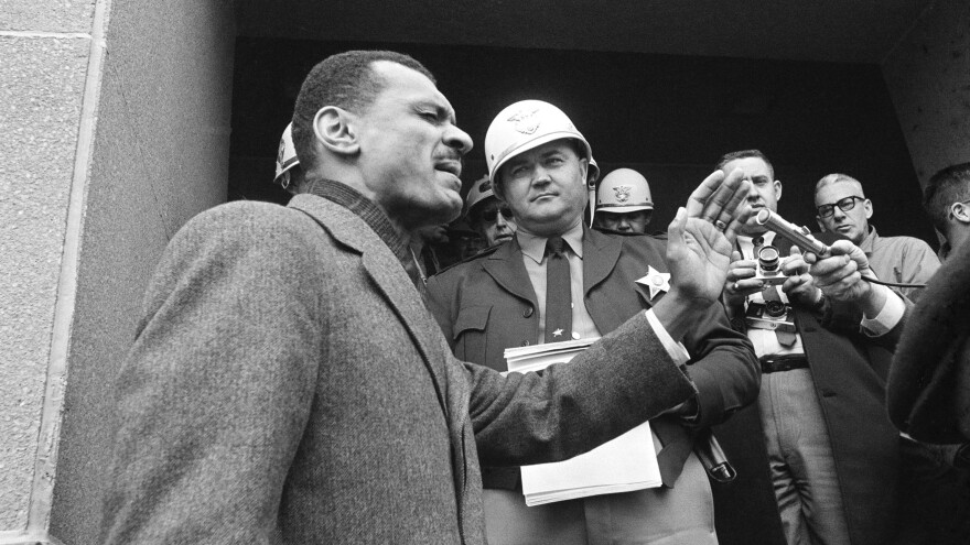 C.T. Vivian, leads a prayer on the steps of the the courthouse in Selma, Ala., in February 1965, after Sheriff Jim Clark (in a white helmet) stopped him at the door with a court order. During another confrontation on the same steps just days later, the segregationist sheriff punched Vivian to the ground — and Vivian stood back up to continue his argument.