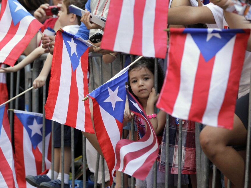 People wave Puerto Rican flags at the National Puerto Rican Day parade last year.