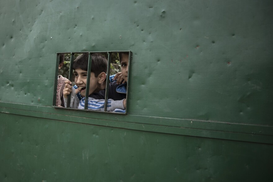 Huzaif, who's 12, and his friend, Danish, look out of an opening of a gate at the martyr's cemetery. During the lockdown, they often come here to spend time and have fun. Most schools have been closed in Kashmir because of the political situation since August 2019. <em>May 18, 2020. Baramulla, North Kashmir.</em>