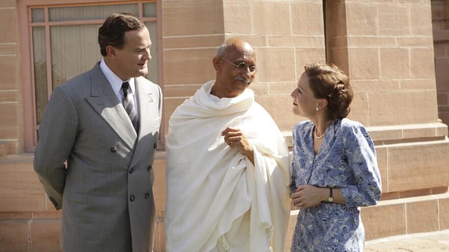 Lord Louis Mountbatten (Hugh Bonneville), Mahatma Gandhi (Neeraj Kabi) and Lady Edwina Mountbatten (Gillian Anderson) smile politely in <em>The Viceroy's House</em>.