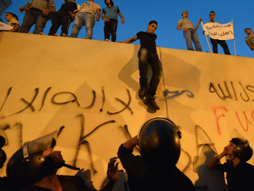 Egyptian riot police stood guard Tuesday as protesters climbed down from the wall of the U.S. Embassy in Cairo during a protest over a film deemed offensive to Islam.