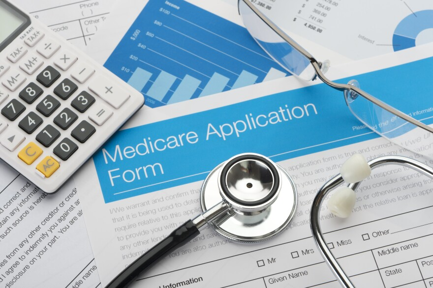 stethoscope and calculator stock photo resting on medicare application paperwork.