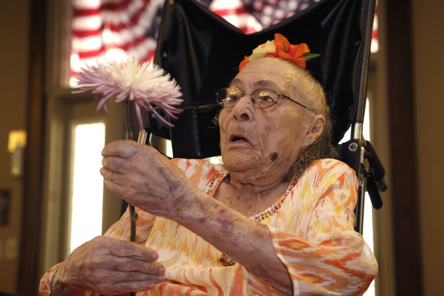 Gertrude Weaver holds a flower given to her a day before her 116th birthday last year, at Silver Oaks Health and Rehabilitation Center in Camden, Ark. Weaver, who last week was named the world's oldest person, died Monday.