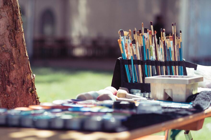 paints and paint brushes are set up near a tree in the sunshine.