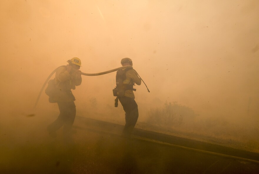 Firefighters battle a fire along the Ronald Reagan Freeway in Simi Valley.