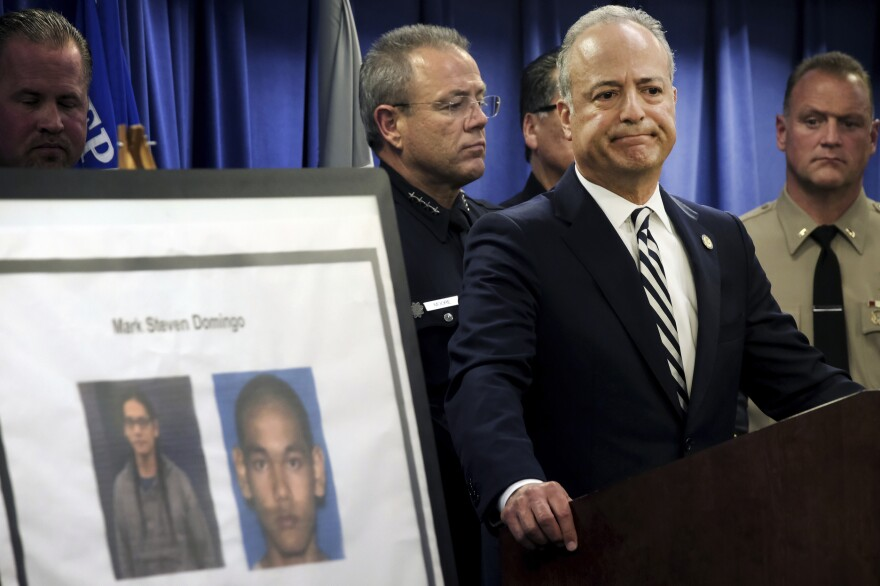 U.S. Attorney Nick Hanna stands next to photos of Mark Steven Domingo during a news conference in Los Angeles on Monday. Federal prosecutors said Domingo had planned to bomb a white supremacist rally as retribution for the New Zealand mosque attacks but was thwarted.
