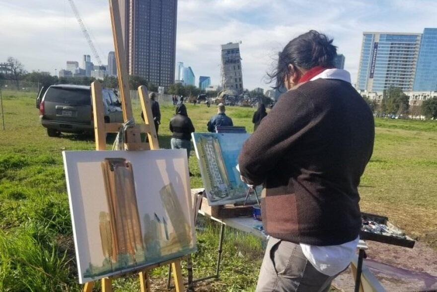 "An artist painting the ""Leaning Tower of Dallas"" shortly before demolition began Monday morning."