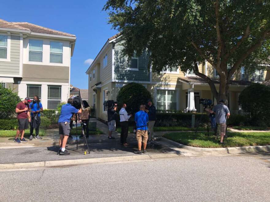 protestors and media stand on a sidewalk outside a pair of townhomes
