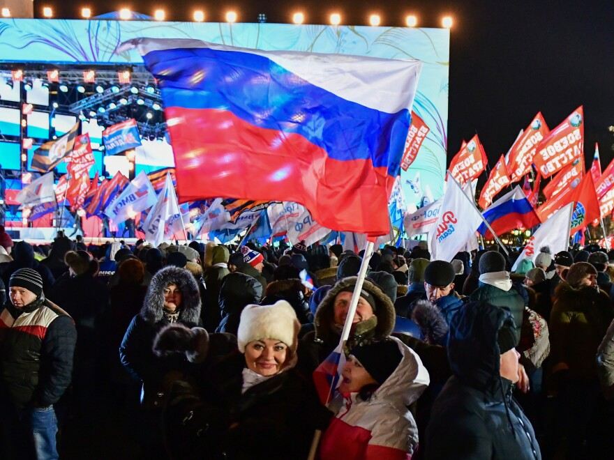 People attend a rally and a concert celebrating the fourth anniversary of Russia's annexation of Crimea at Manezhnaya Square in Moscow on Sunday. The controversial move to take Crimea became a proud event for some voters who handed Vladimir Putin a broad election win, timed for the same date as the anniversary.