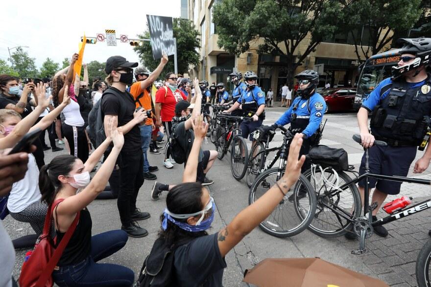 Protesters against police violence face a line of Austin police officers in downtown on May 31.