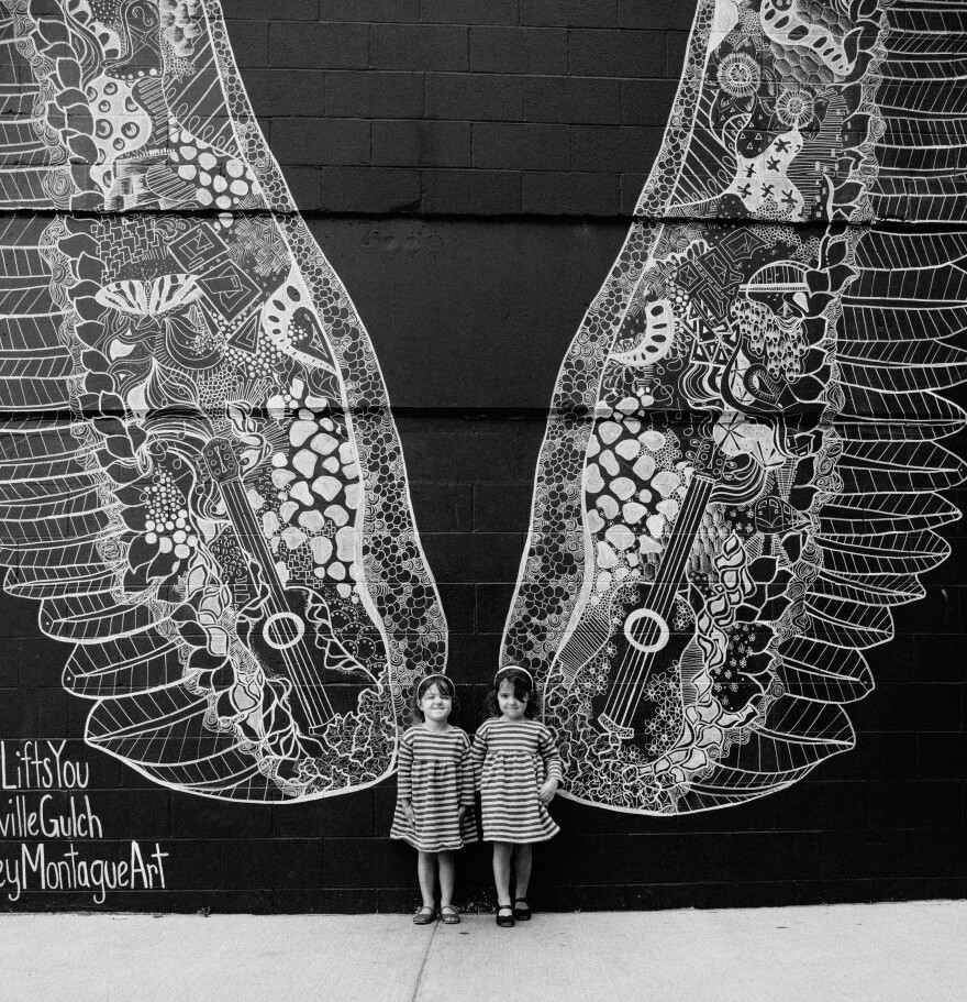 Kelsey Montague painted these 20-foot tall wings on the side of a building in The Gulch. All day long, people stand in front of them to have their pictures taken. It's called <em>What Lifts You</em>, and it does.