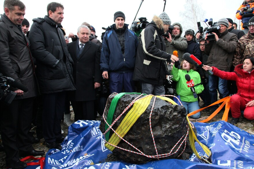People look at what scientists believe to be a chunk of the Chelyabinsk meteor, recovered from Chebarkul Lake near Chelyabinsk, about 930 miles east of Moscow.