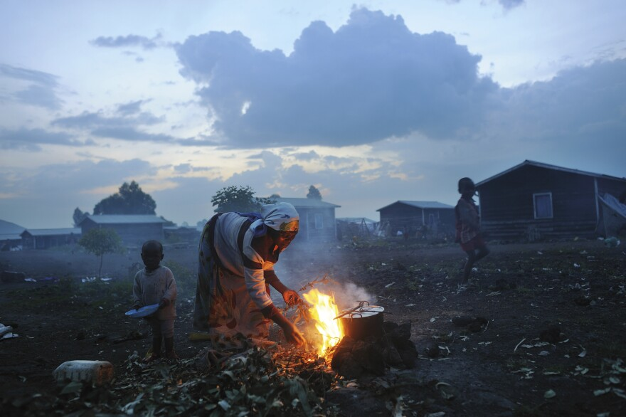 A Congolese woman displaced because of fighting cooks in the evening at Kibati camp in Goma, in eastern Congo. November 26, 2008