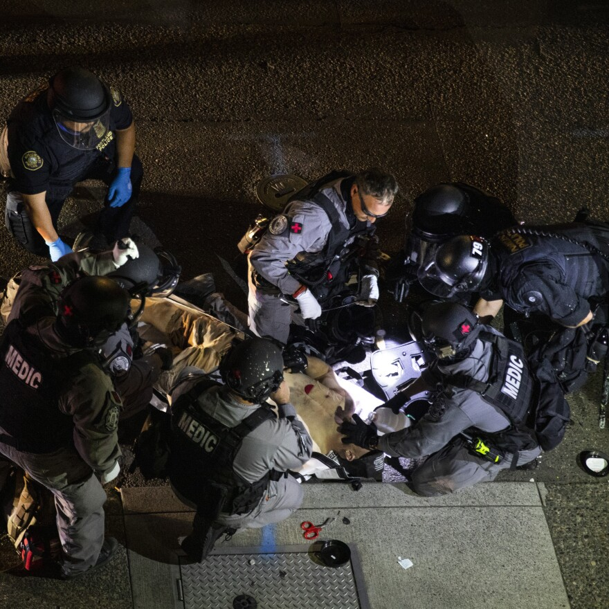 Emergency personnel treat Aaron Danielson in Portland, Ore., on Saturday. The man suspected of killing Danielson, Michael Reinoehl, was killed by law enforcement agents as they attempted to arrest him Thursday night.