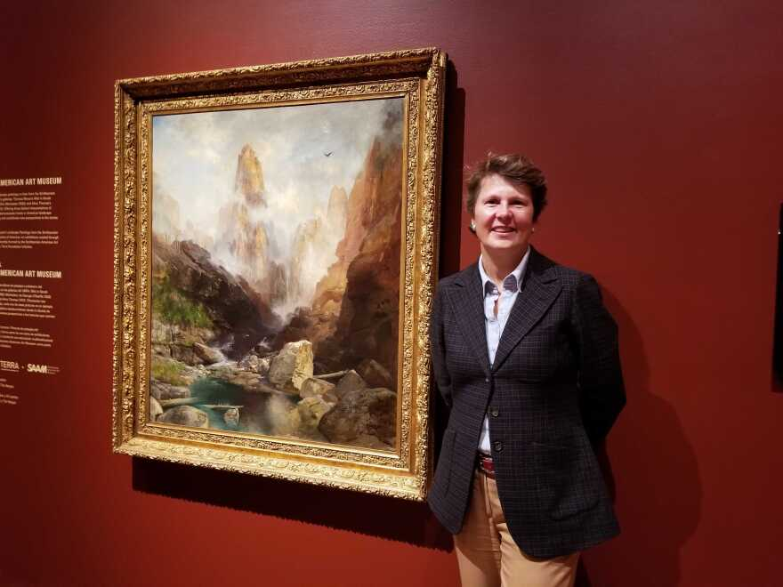 A woman standing in front of a large nineteenth century painting hanging in a museum.