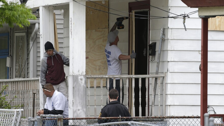 Workers board up the house where three women were held in Cleveland Saturday. Suspect Ariel Castro, who allegedly held three women captive for nearly a decade, is charged with rape and kidnapping. Sunday, the women asked for privacy and time to connect with their families.