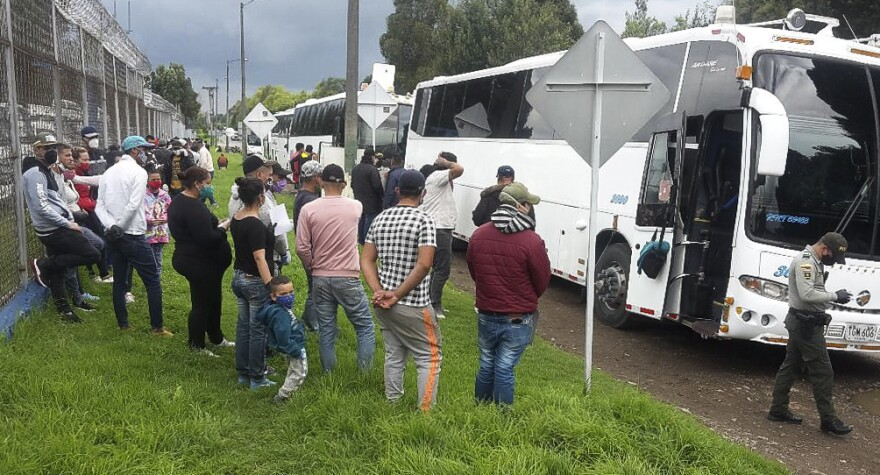 Venezuelans, who chartered buses in Bogotá for the 450-mile trip to the Venezuelan border, wait as the vehicles are inspected by police and health officials. These buses had hit so many roadblocks and delays that after 24 hours they had traveled just 10 miles from the Colombian capital.