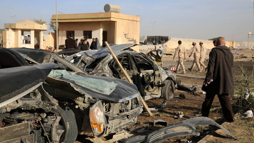 Security officers and other people walk next to damaged cars at the site where a truck bomb exploded at a security training camp on Thursday in the northwestern coastal city of Zliten, Libya.