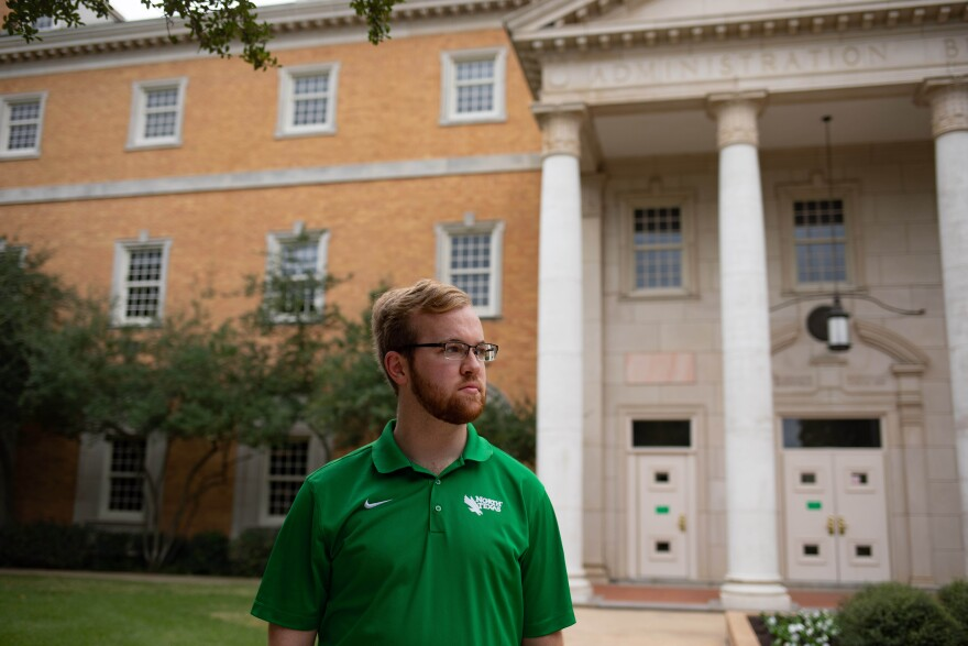 Michael Luecke looks away as he stands outside of a campus building.