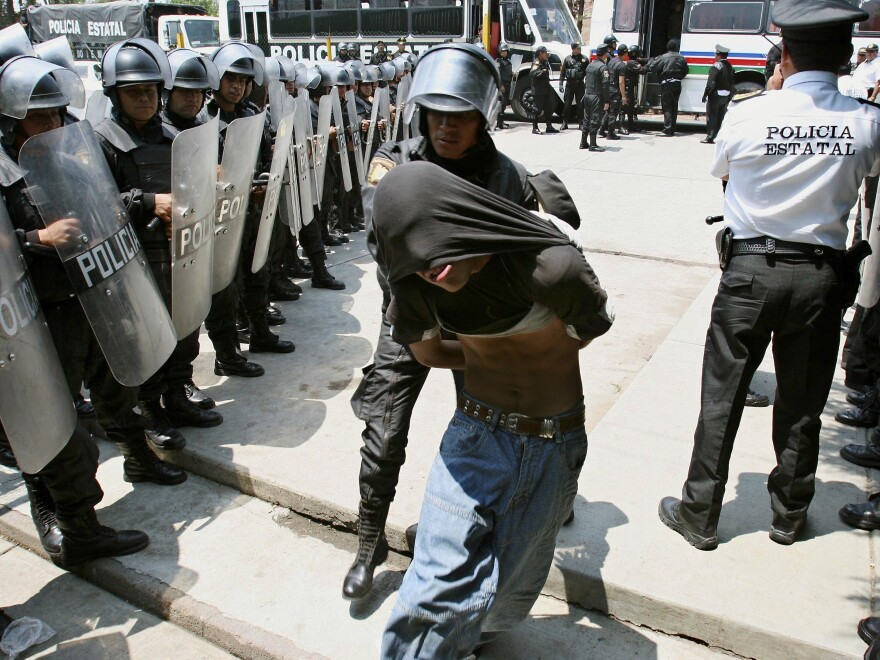 A protester who clashed with state riot police in the town of San Salvador Atenco is taken into the Santiaguito prison in Almoloya de Juarez, Mexico in 2006. Hundreds of police fired tear gas and pushed through human barricades to take control of the town.