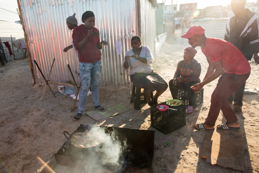 Many residents don't having proper cooking facilities in their shacks (or money to buy items in bulk). So street food is common. Linda Maseko (left, wearing jeans) has a bite with other residents.