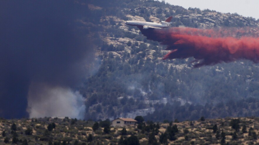 An aerial tanker drops fire retardant on a wildfire threatening homes near Yarnell, Ariz., on July 1. An elite crew of firefighters was overtaken by the out-of-control blaze on June 30, killing 19 members as they tried to protect themselves from the flames under fire-resistant shields.