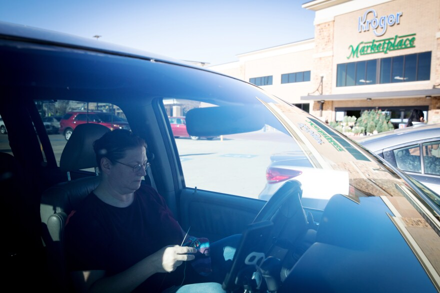 Teri Smith knits a pair of socks in a Kroger parking lot in Arlington, Texas, while she waits for Instacart to offer her a new grocery order. She signs up for shifts with Instacart five or six days a week.