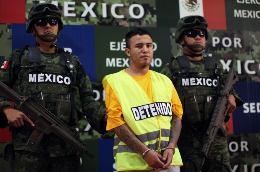 "Army soldiers flank Daniel Ramírez, alias ""El Loco,"" during his presentation to the media in Mexico City on Monday."