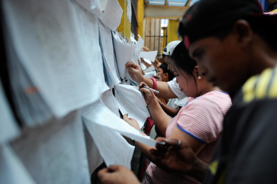 Voters look for their names and assigned precincts at a public elementary school on Sunday in Manila.