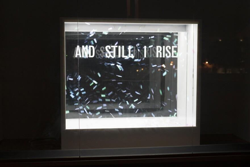 Confetti hangs in an open window reminiscent of a snowglobe in Bunny Burson's sculpture