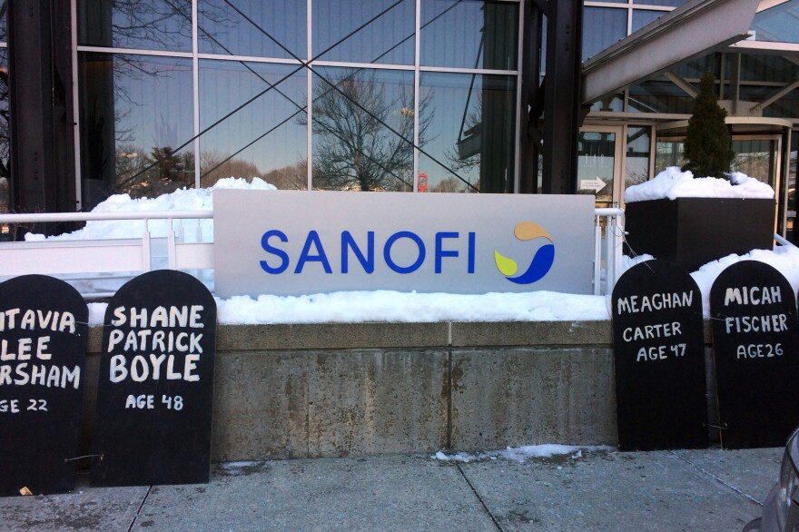 Cardboard headstones line the sidewalk outside of pharmaceutical company Sanofi's Cambridge, Mass., offices. The Right Care Alliance held a protest against high insulin prices, which have led some to the dangerous practice of cutting doses to save. (Anna Bauman/On Point)