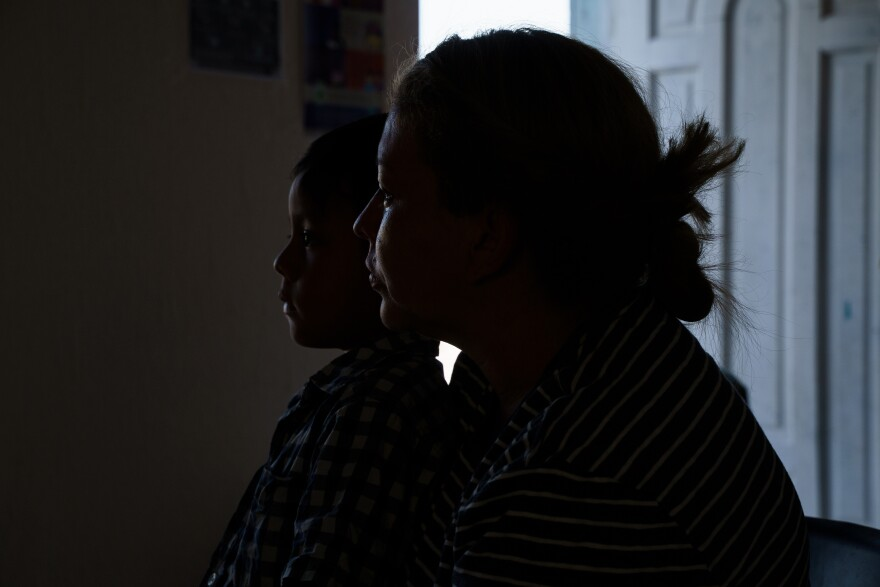 Levis and her son sitting in shadow with an open door in the background.