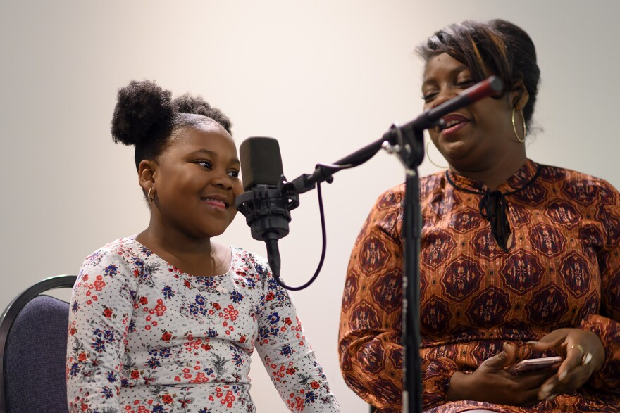 "Six-year-old Rae Reece, at left, tells a story about ""the best day ever"" during St. Louis Public Radio's We Live Here"" house party Nov. 27 as storytelling coach Chiffontae Ross looks on."