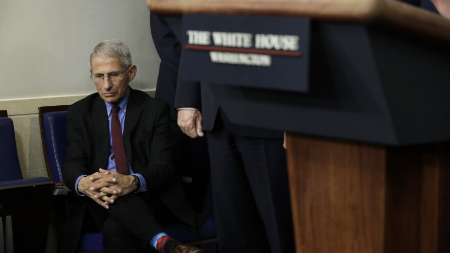 Dr. Anthony Fauci, director of the National Institute of Allergy and Infectious Diseases, listens as Trump speaks at a briefing on March 27.