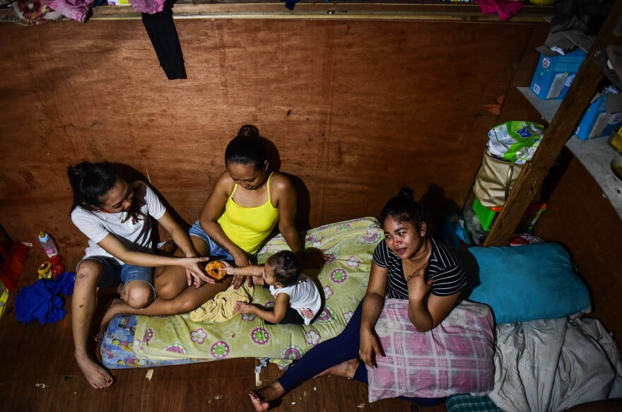 """Baby Roseann plays with her two aunts and mother Rachel Quebec (far right) in their small house. Roseann's father, Clarence Jepadre, 17, was stabbed and killed last year. His body was found with a packet of marijuana and a note saying, """"I'm a pusher... Don't be like me."""""""