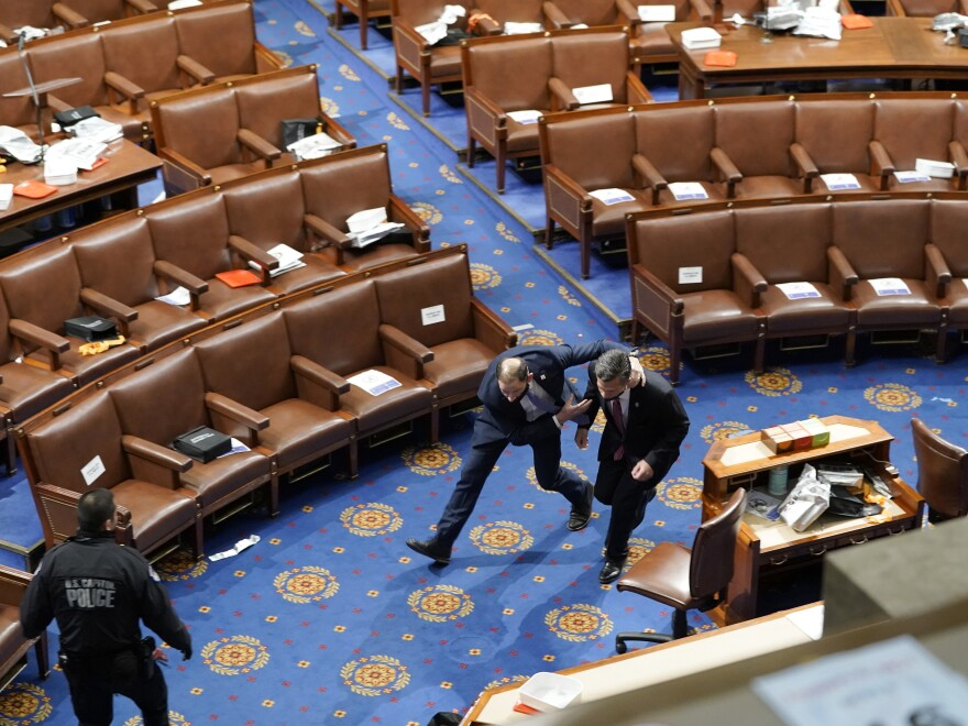 Members of Congress run for cover as rioters try to enter the House chamber on Jan. 6.