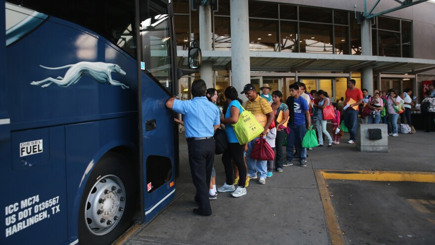 """Immigrants board a bus after being released from U.S. Border Patrol detention in Texas last month. An immigration judge says the Obama administration's """"fast-tracking"""" effort means many people go into court without an attorney, opening a door to future problems."""