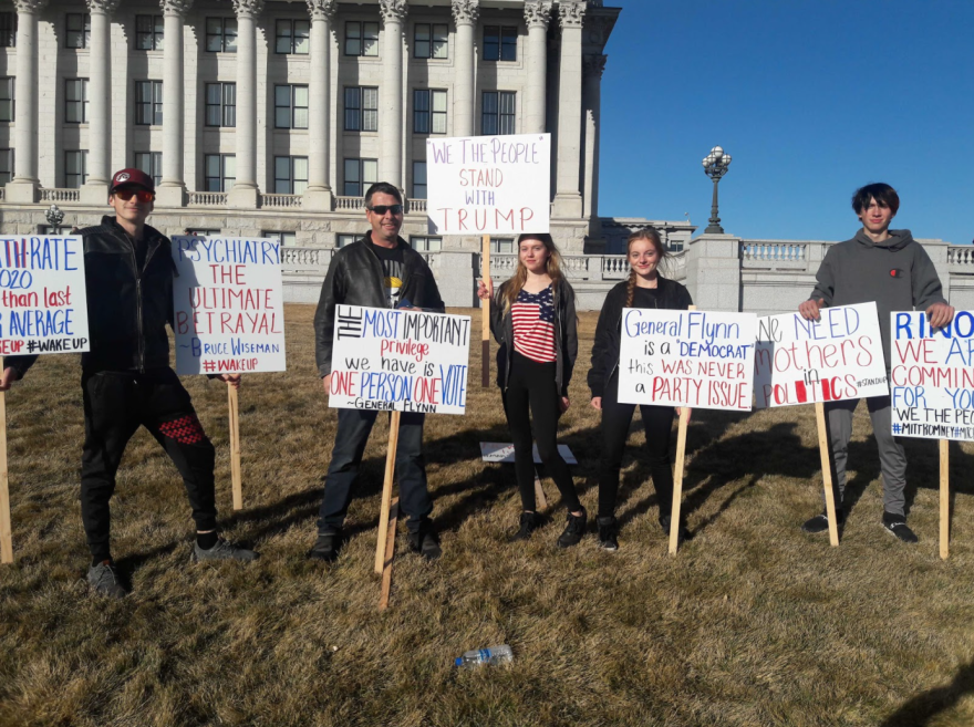 Joseph Carlisle and his family pose with signs they made for Wednesday's Trump rally at the Utah Capitol.