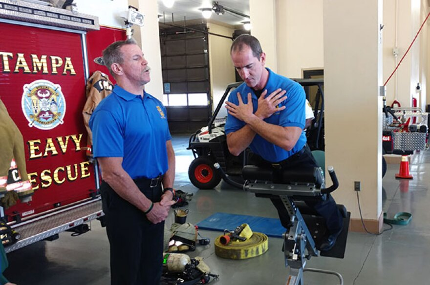 Tampa Fire Rescue Engineer-Driver John Cannon (left) spots for Capt. Jeremy Finney as he demonstrates the Variable Angle Roman Chair in TFR's Station 1.