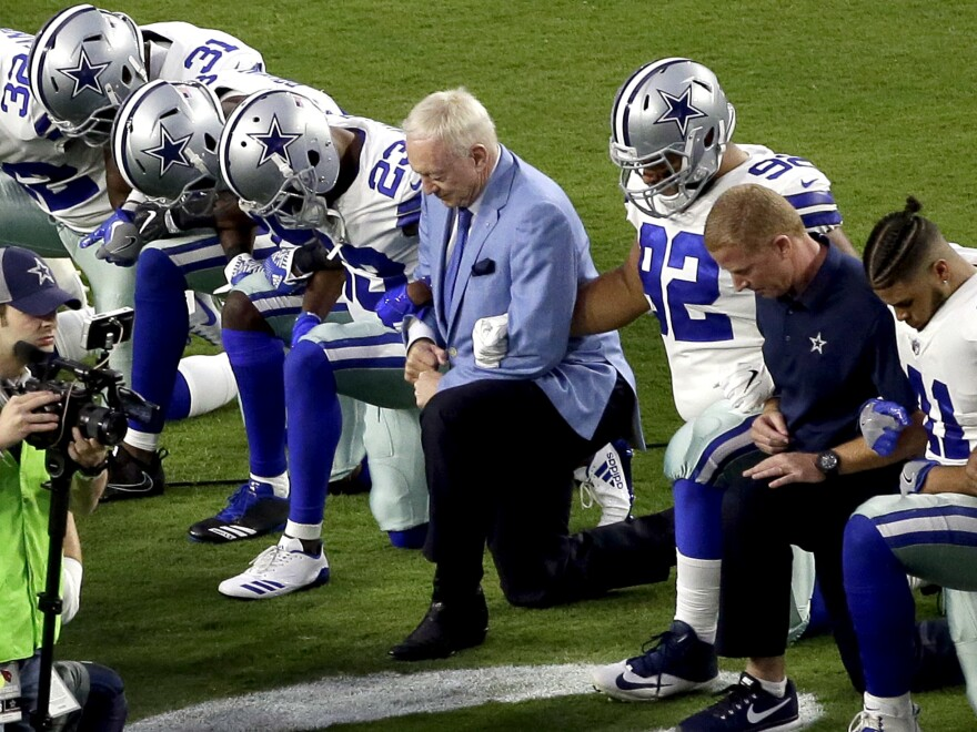 The Dallas Cowboys, led by owner Jerry Jones, take a knee prior to the national anthem at a game against the Arizona Cardinals on Sept. 25 in Glendale, Ariz.