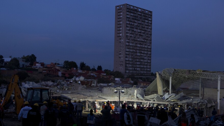 Rescue workers and police stand around the scene Thursday night as the search for survivors continues among the wreckage of a maternity and children's hospital in Cuajimalpa on the outskirts of Mexico City.