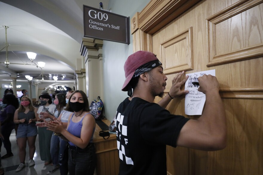 Matthew Bruce of Des Moines, Iowa, signs a note during a Black Lives Matter demonstration outside Iowa Gov. Kim Reynolds' office in June. The Republican governor has signed an executive order restoring voting rights to people convicted of a felony.