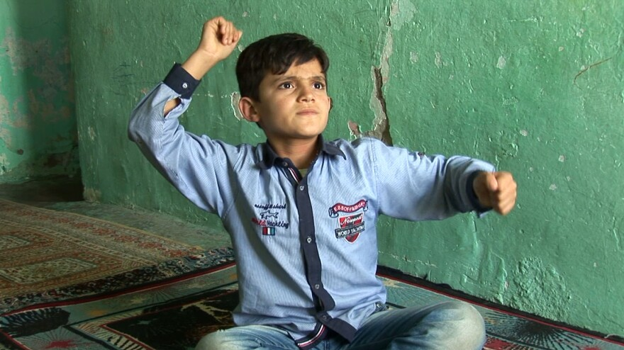 A boy describes the bombing of his village in Erkan Özgen's 2016 video <em>Wonderland.</em>