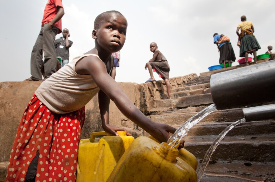 A child in a neighborhood in Kampala, Uganda, fills a container with water.