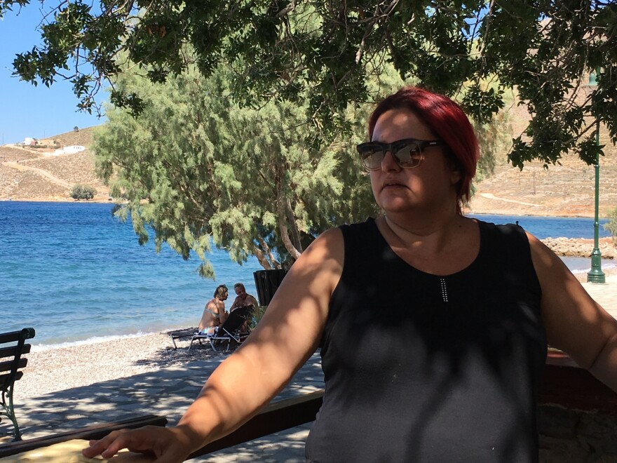 """Tilos Mayor Maria Kamma sits outside a seaside cafe. """"We wanted to evolve from simply a green island into a clean-energy island,"""" she says. """"We wanted to do something substantive."""""""